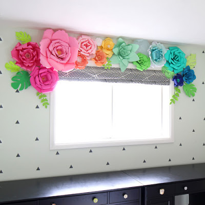A rainbow of 3D paper flowers create the focal point in this room's decor