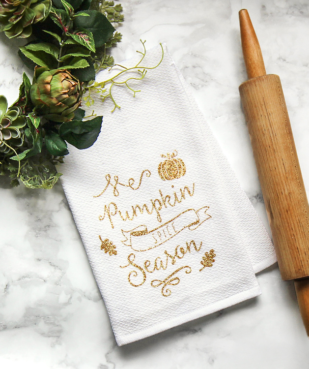 Make your own custom tea towel for fall using glitter heat transfer vinyl and a Silhouette or Cricut machine. It's a cute and easy fall craft to decorate your home.