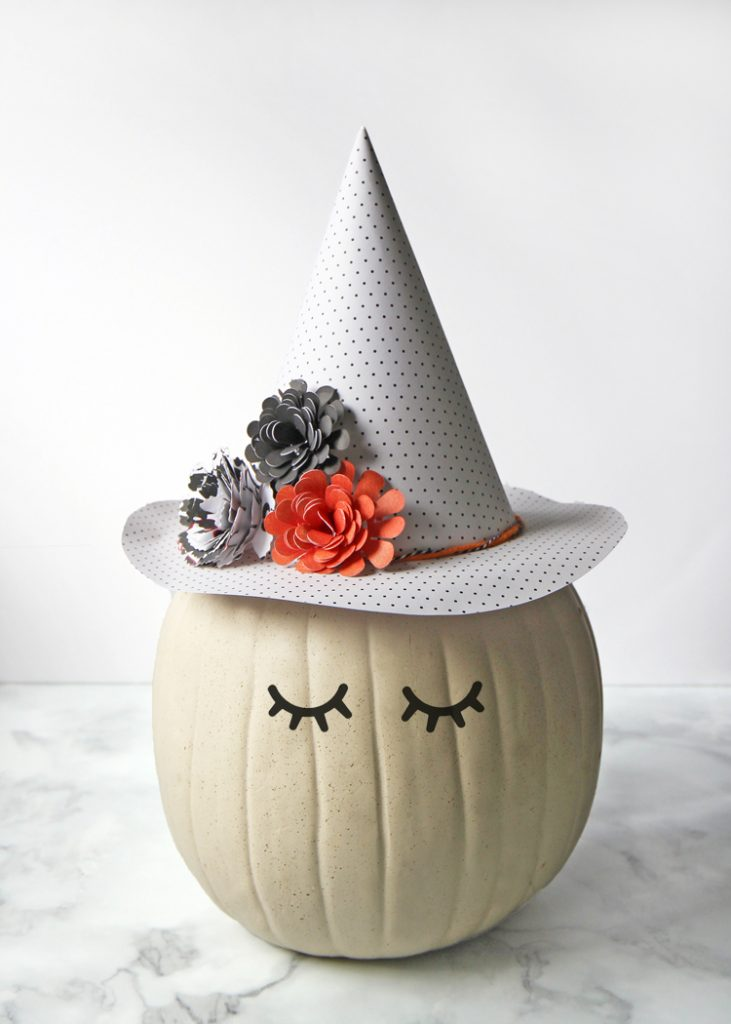 This no-carve pumpkin decorating idea features an adorable witch with a floral and polka dot hat made of paper.