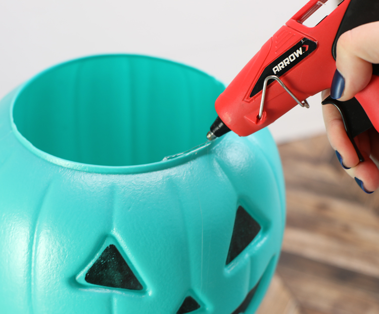 gluing plastic pumpkin buckets together
