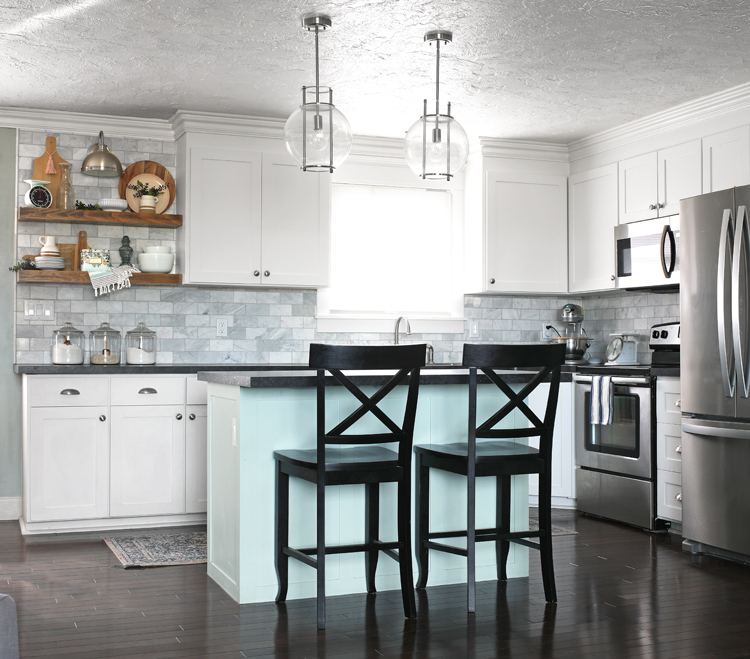 counter height black bar stools in a white kitchen with blue island