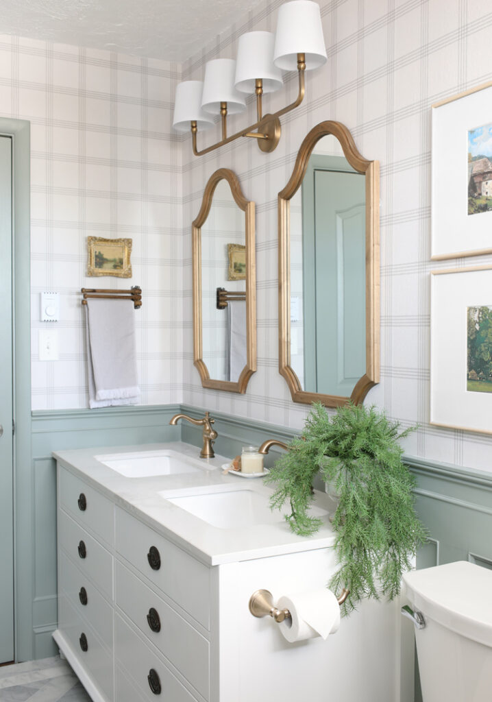 white vanity, plaid wallpaper, wood mirrors, gold hardware and light fixture, antique cabinet pulls
